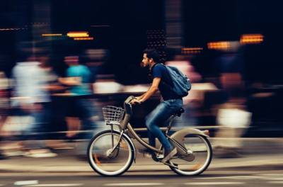 man bycicling through town